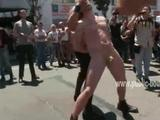 Naked and gay slave is flogged has his mouth covered and his nipples pinched in a public street while forced to lick another gay man ...